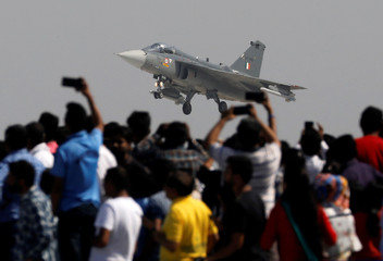 """Spectators take pictures as the Indian Air Force (IAF) light combat aircraft """"Tejas"""" approaches to land during the Indian Air Force Day celebrations at the Hindon Air Force Station on the outskirts of New Delhi"""