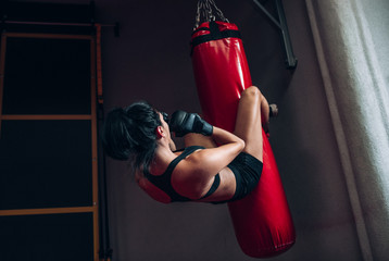 Rear view image of young woman boxer hitting a huge punching bag at a boxing studio. Sportswoman kickboxer training hard in the gym. Sport, lifestyle and people concept.