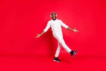 Full body photo of amazing dark skin man listening favorite playlist in earflaps moving with rhythm down street wear knitted sweater trousers isolated red background