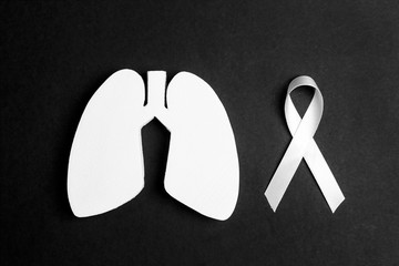 White lung cancer awareness ribbon and lung symbol on black background.  Black and white image.