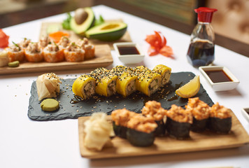 Tasty and delicious lunch from three courses in luxury Japanese restaurant. Gourmet set from sushi rolls served with soy sauce, wasabi and marinated ginger. Oriental meal made from rice and seafood.