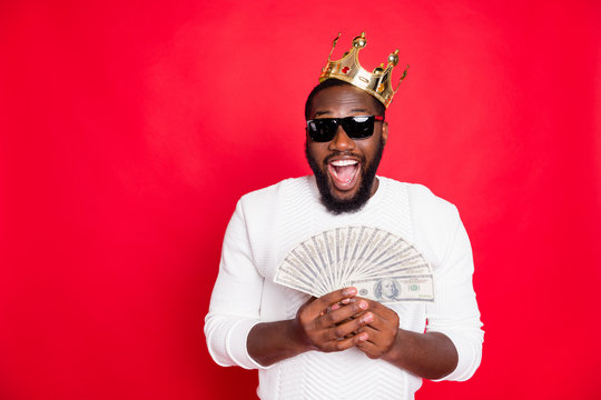 Portrait of amazed surprised crazy funky dark skin man with brown hair beard hold fan money win jackpot in x-mas casino got profit become millionaire wear white jumper isolated red color background