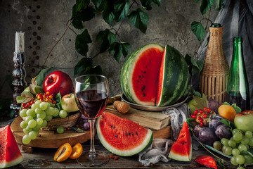 Classic still life with fruit and a glass of red wine. Fruits on a concrete dark background with a vine. rustic style. The concept of rural life.