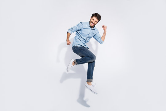 Full size profile photo of funny indian guy jumping high rejoicing raising fists crazy competitive mood wear casual denim clothes isolated white color background
