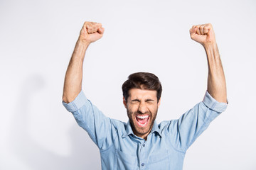 Photo of arab guy celebrating lottery winning raising arms up rejoicing yelling of incredible feelings wear casual denim shirt isolated white color background