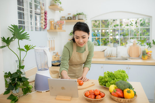 Woman cutting vegetables in kitchen while watching tablet in front of her