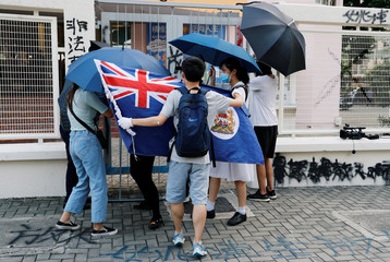 A man holds a colonial flag of Hong Kong as he protests against the punishment of those students who fight to protect the Lennon walls, one of the symbols of anti-government protest, outside Po Leung Kuk Yao Ling Sun College, in Hong Kong