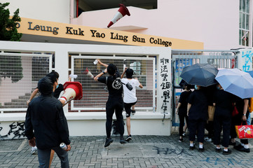 Protesters throw traffic cones into a school to protest against the punishment of those students who fight to protect the Lennon walls, one of the symbols of anti-government protest, outside Po Leung Kuk Yao Ling Sun College, in Hong Kong