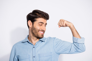 Photo of amazing handsome guy raising arm showing perfect biceps shape expressing strength wear casual denim shirt isolated white color background
