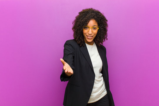young black business woman smiling, looking happy, confident and friendly, offering a handshake to close a deal, cooperating