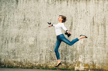 Outdoor portrait of happy young woman jumping high up in the city