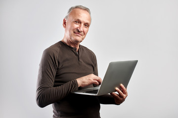 Stylish elderly man with laptop in hands pays for services and buys goods over the Internet with home delivery isolated on white background, online store