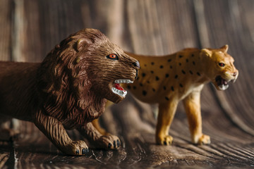 figure of a toy Cheetah and a lion next to a wooden background