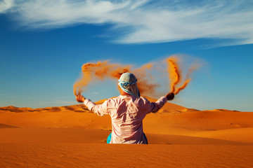 In de dag Marokko Single Man throws sand in the Sahara desert at sunset.
