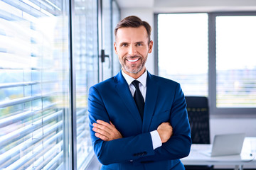 Portrait of successful businessman standing in corner office