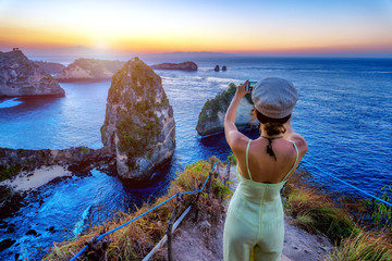Vacation lifestyle concept, Female tourist standing take a picture with smartphone at Nusa Penida Island Bali, Indonesia.