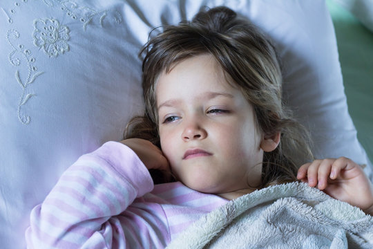 Sick and tired child wrapped with blanket lying in bed. Close up. Health care and illness concept.