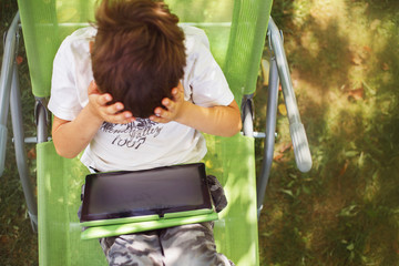 boy sitting with a tablet and covered his face with his hands.  the boy lies on a deck chair and plays on the tablet. child with a gadget
