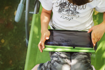 boy sitting with a tablet in the garden. the boy lies on a deck chair and plays on the tablet. child with a gadget