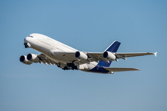 Blank unlabeled Airbus A380 4-engine jet airliner starting at the frankfurt airport takeoffairplane concept