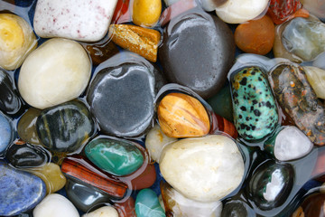 Flat lay of colorful polished (tumbled) stones in shallow water