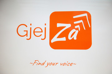 """GjejZa"" app logo is pictured on a screen during a presentation in Tirana"