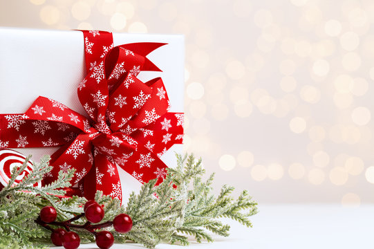 Christmas white gift box with red ribbon with snowy foliage and red berries over a light background with natural bokeh and copy space.