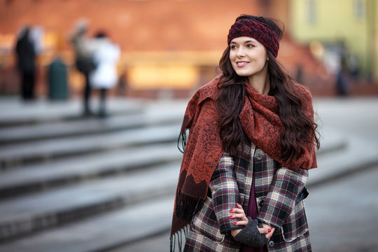 Beautiful joyful woman portrait in a city. Smiling  girl wearing warm clothes and hat  in winter or autumn