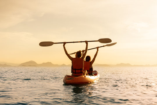 Couple kayaking together. Beautiful young couple kayaking on lake together and smiling at sunset
