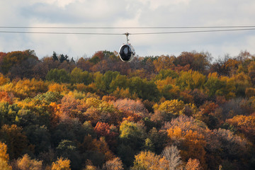 A cable car moves over the trees with autumn coloured leaves in Moscow