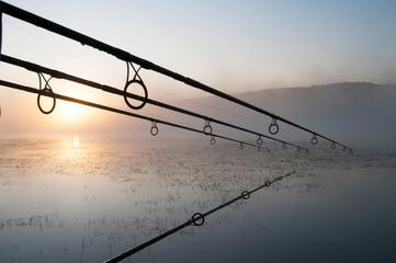 Printed kitchen splashbacks Fishing fisherman with fishing rods at sunrise on the lake