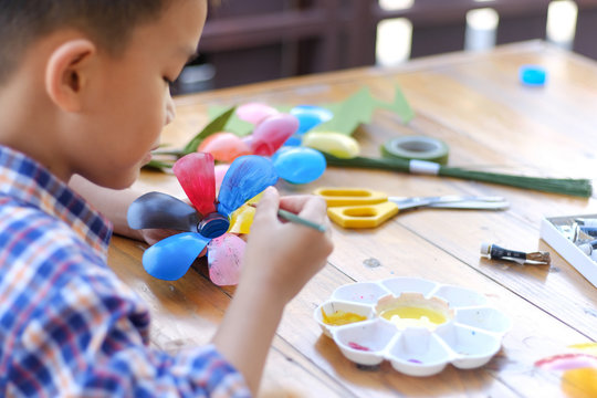 Asian boy painting a colourful plastic flower made from water bottle on wooden table outdoor.Recycled colorful plastic flowers.Recycle decoration.