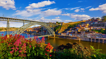 Fototapete - Porto, Portugal. Evening sunset picturesque view at old town with antique houses and red roofs near bridge Ponte de Dom Luis on river Douro.