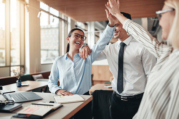 Laughing businesspeople high fiving together in an office