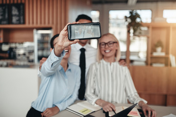 Laughing businesspeople taking selfies with a cellphone at work