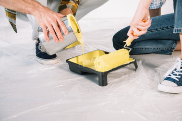 cropped view of man adding yellow paint into roller tray and woman holding paint roller