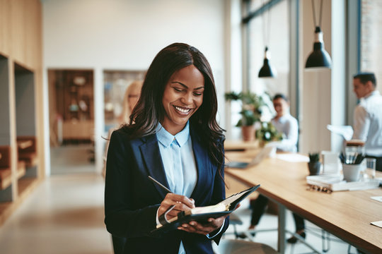 Smiling African American businesswoman writing notes in a modern