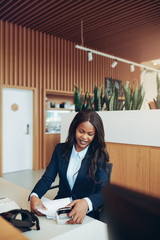 Smiling African American businesswoman sorting documents at a re