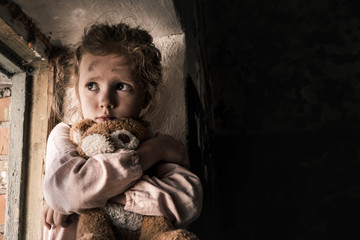 frustrated child holding teddy bear in dirty room, post apocalyptic concept
