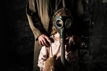 cropped view of man standing near kid in gas mask, post apocalyptic concept