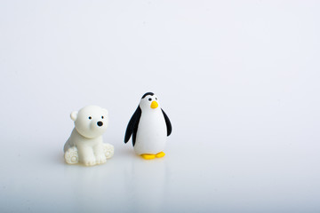 Penguin and polar bear rubber toys, cute animal shaped rubber doll isolated in white background.