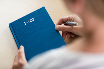 Close Up Of Woman Opening New Year 2020 Diary On Table