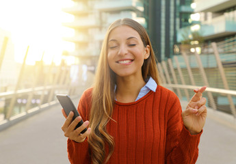 Pretty hopeful girl crossing fingers and bites lip holding a smart phone waiting for news outdoor. Young woman with crossed fingers and smart phone wishing the best outside.