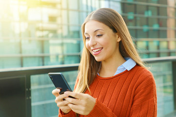 Young business woman wearing orange sweater texting on the smart phone out of the office in a sunny day.