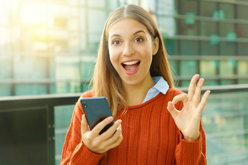 Happy beautiful autumn woman holding smart phone doing Ok sign at the camera. Excited satisfied young woman using smart phone outdoors.