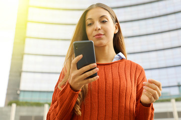 Confident business woman using smart phone with modern skyscraper on the background.