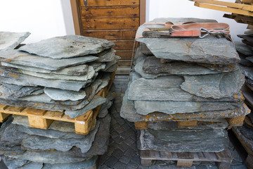 detail view of stone granite and slate roof tiles ready for putting onto a house roof