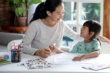 happy mother teaching her daughter the basic to read and write at home. toddler kindergarten student