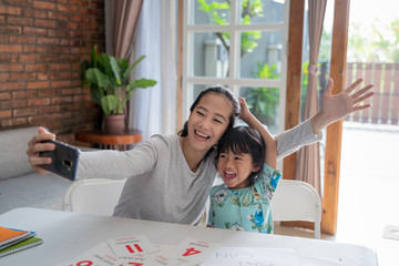 happy asian mother and kid taking selfie together at home