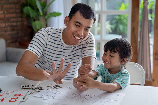 toddler learning math and counting with her father at home together